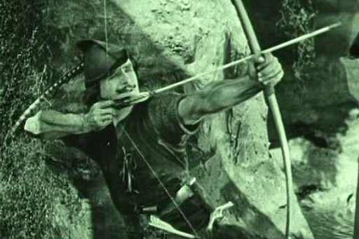 Douglas Fairbanks as Robin Hood shoots an arrow