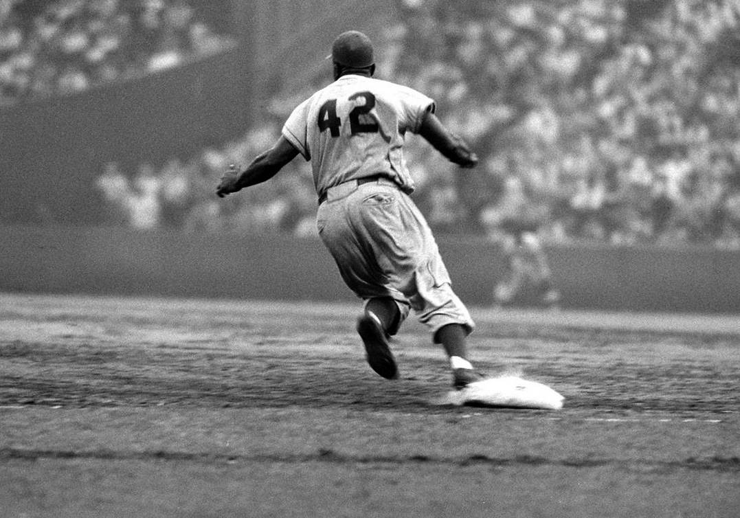 Jackie Robinson rounds first base in a 1956 game against the New York Giants.