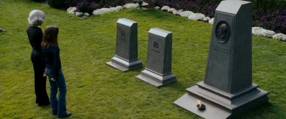 "Storm and Kitty Pryde contemplate the gravestones of Jean Grey, Scott Summers and Charles Xavier in ""X Men: The Last Stand"""